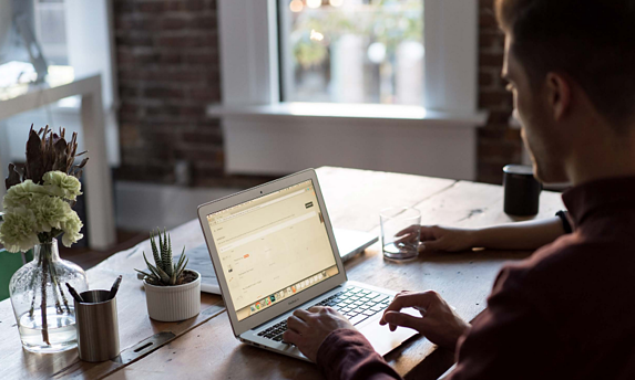 Person on laptop sat at a desk as part of market research online community ideas