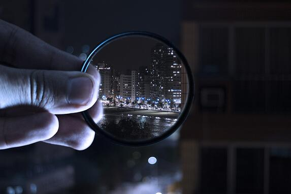 Magnifying glass looking through a city scape to represent social grades in market research