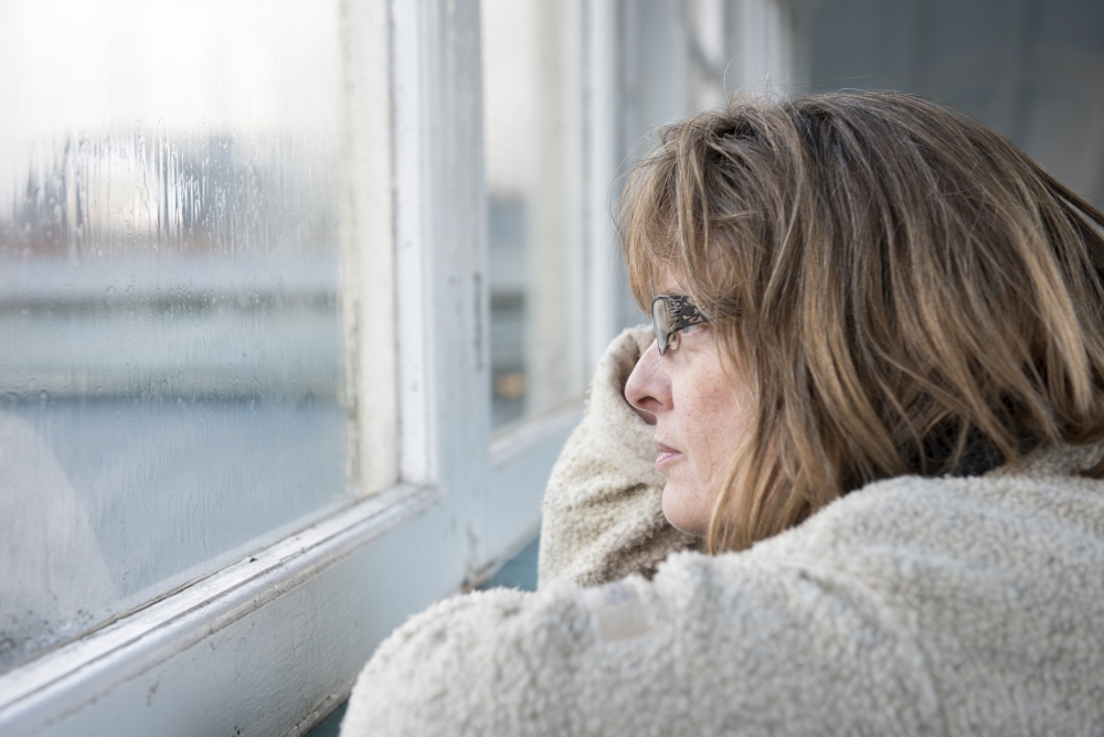 mature woman looking out of the window on a rainy miserable day