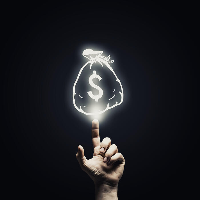 Human hand pointing with finger at money sign
