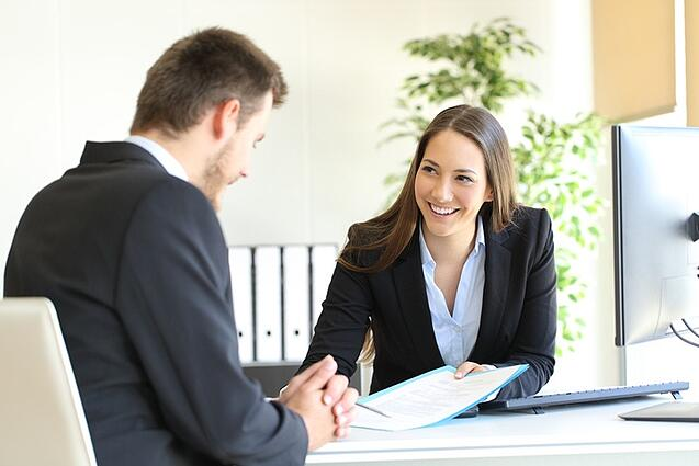 Young business woman smiling while working with a client.