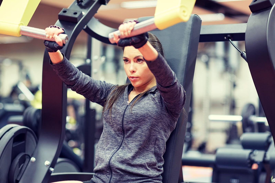 woman-flexing-muscles-on-chest-press-gym-machine-PF3E8HU-min