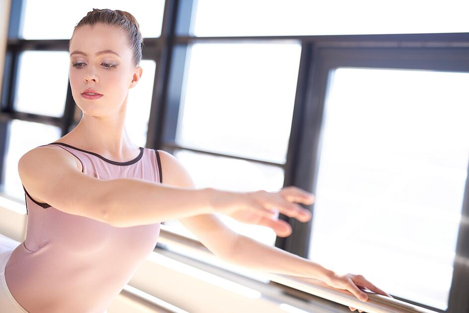 young-ballerina-warming-up-in-sunny-studio-PM84D8M-min