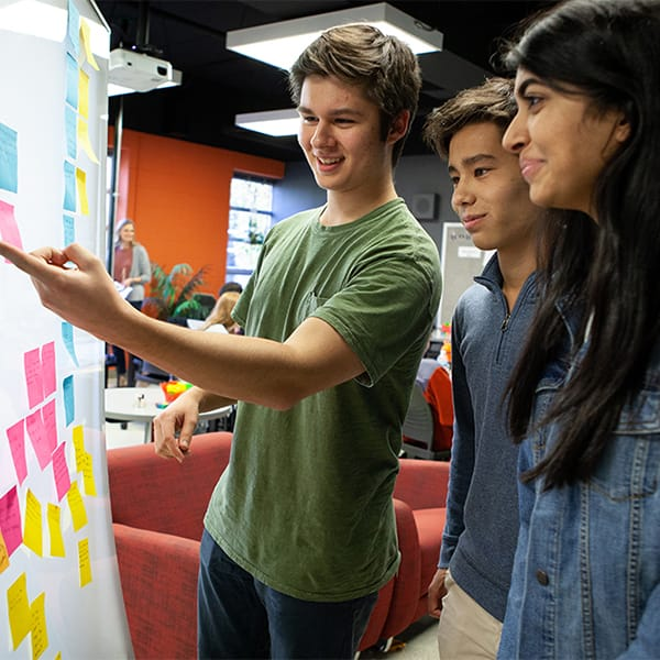 Student showing fellow students ideas on white board.
