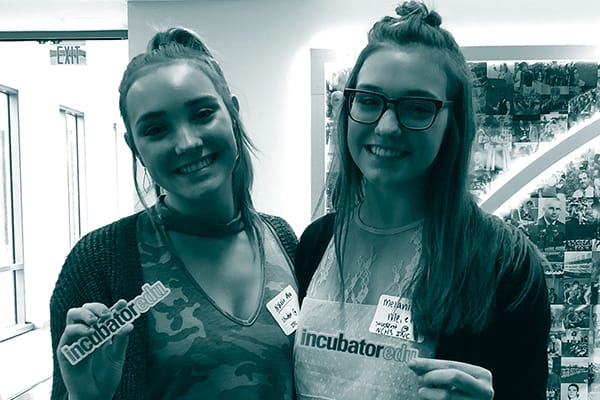 Two female students holding stickers