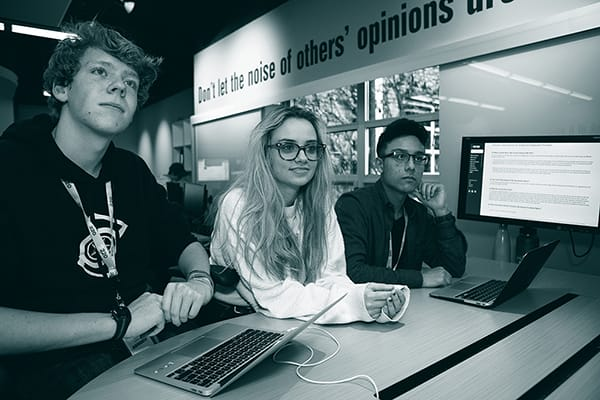 Three students at a table with computers