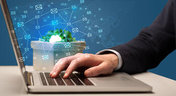Businessman hand sending a bunch of messages on laptop with cloud computing concept
