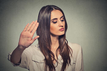 Closeup portrait young annoyed angry woman with bad attitude giving talk to hand gesture with palm outward isolated grey wall background. Negative human emotion face expression feeling body language