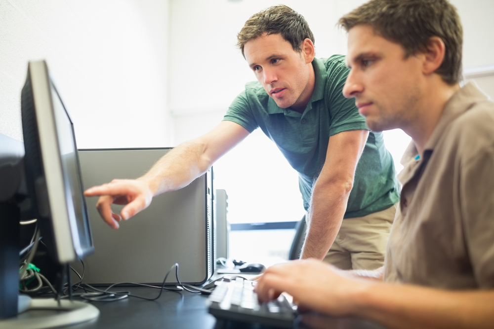 Side view of teacher showing something on screen to mature student in the computer room