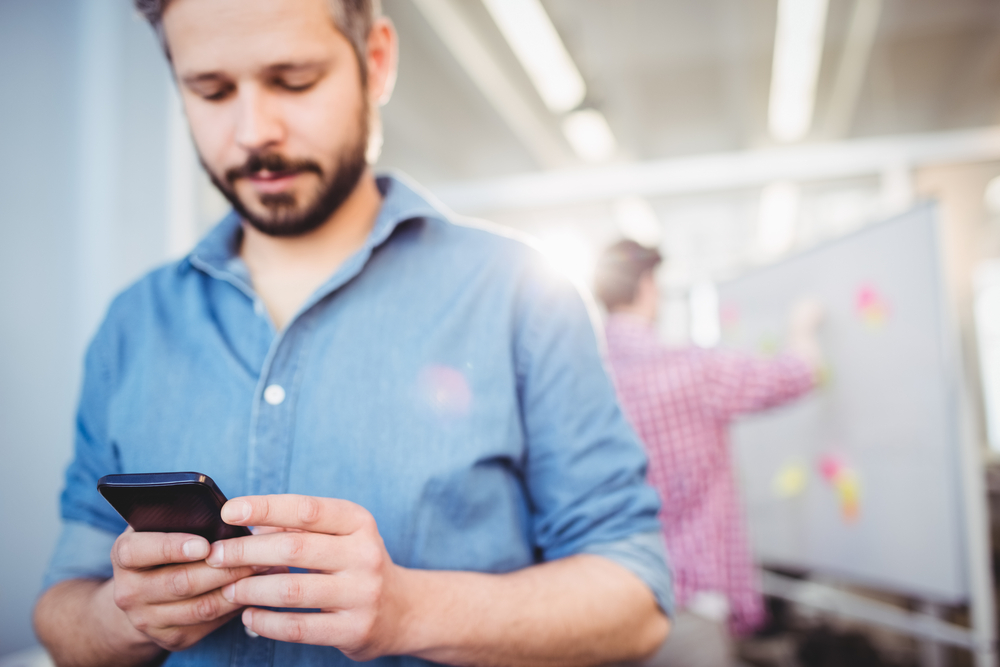 Young businessman texting on cellphone at creative office
