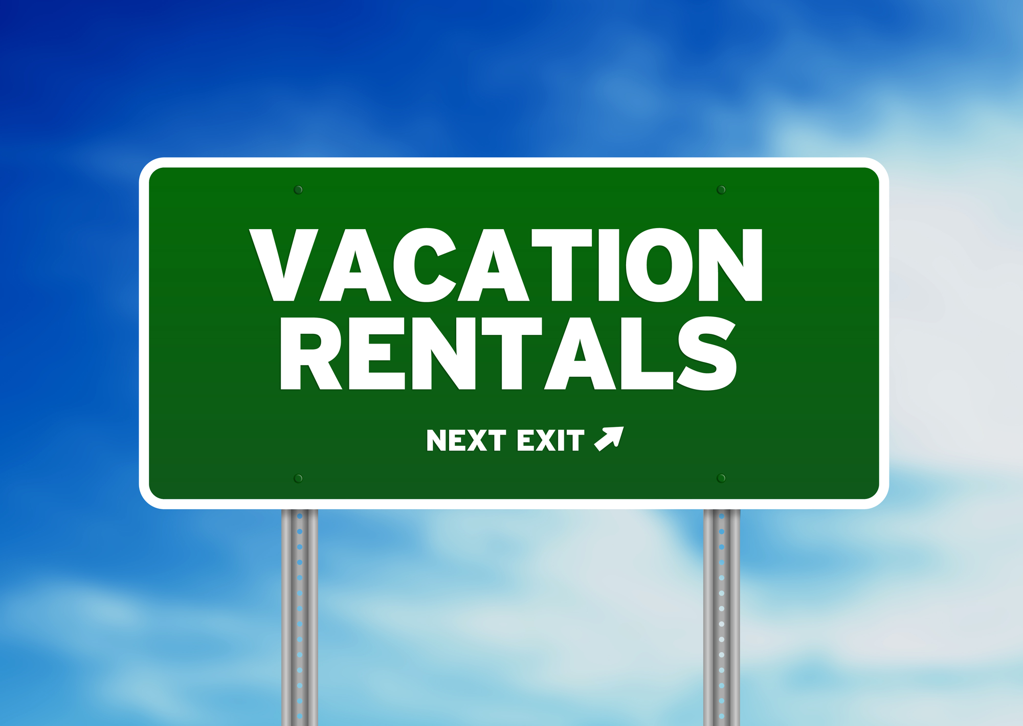 """Green road sign with """"VACATION RENTALS NEXT EXIT"""" displayed"""