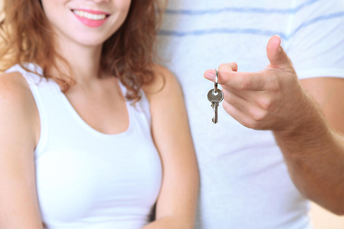 Young couple with keys to your new home close-up