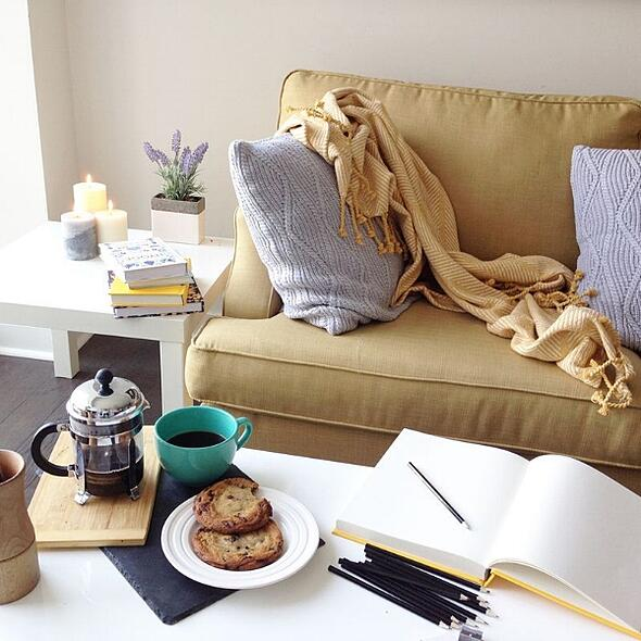 Small space living made more Hygge with natural light and candles; photo courtesy of  Bec Jager