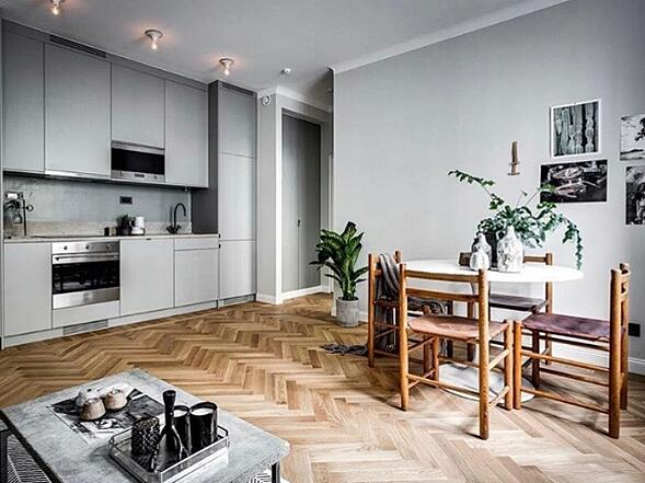 Scandinavian apartment mixes wood floors with an unfinished stone top coffee table, plus wood accented table and chairs, and green plans; Photo Courtesy of  Henrik Nero