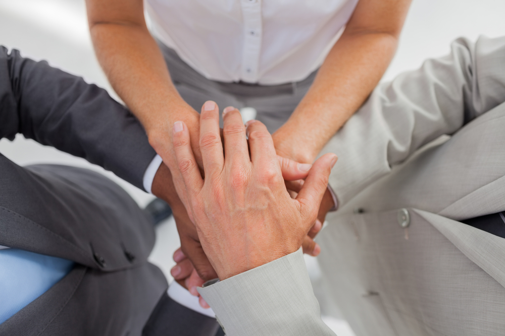Business%20people%20gathering%20their%20hands%20together%20in%20the%20workplace