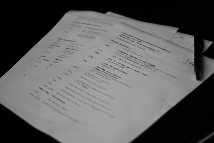 a printed out live event production schedule explaining an hourly and daily overview