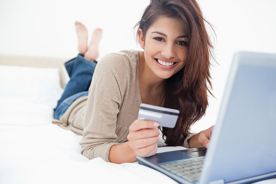 A woman smiling and looking in front of her as she uses her credit card with her laptop.