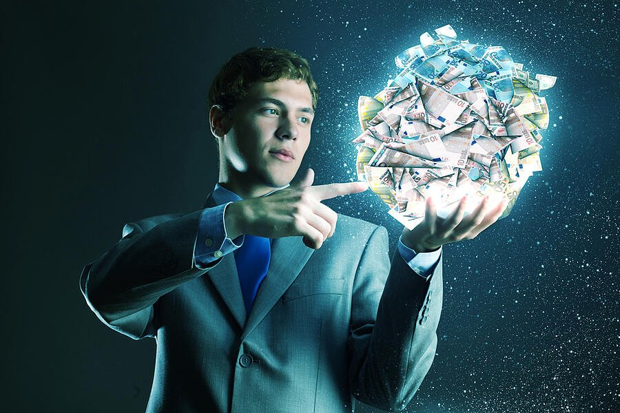 Businessman holding ball of money in hand