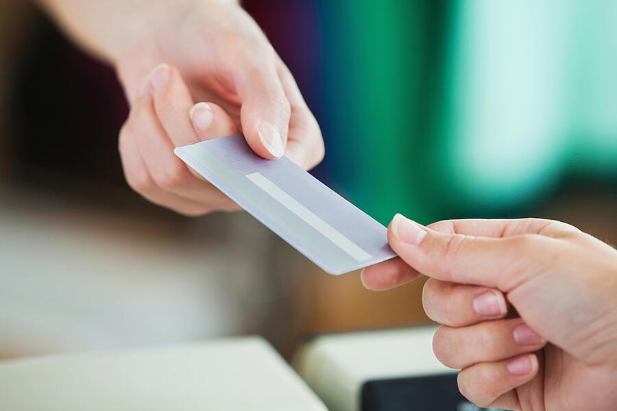 Close-up of a young woman paying with her credit card in a shop