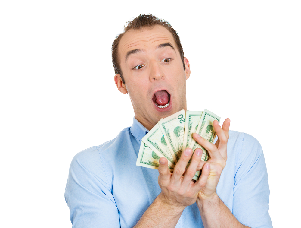 Closeup portrait of super happy excited successful business man, funny looking guy holding money dollar bills in hand, isolated on white background. Positive human emotions, facial expression feeling.