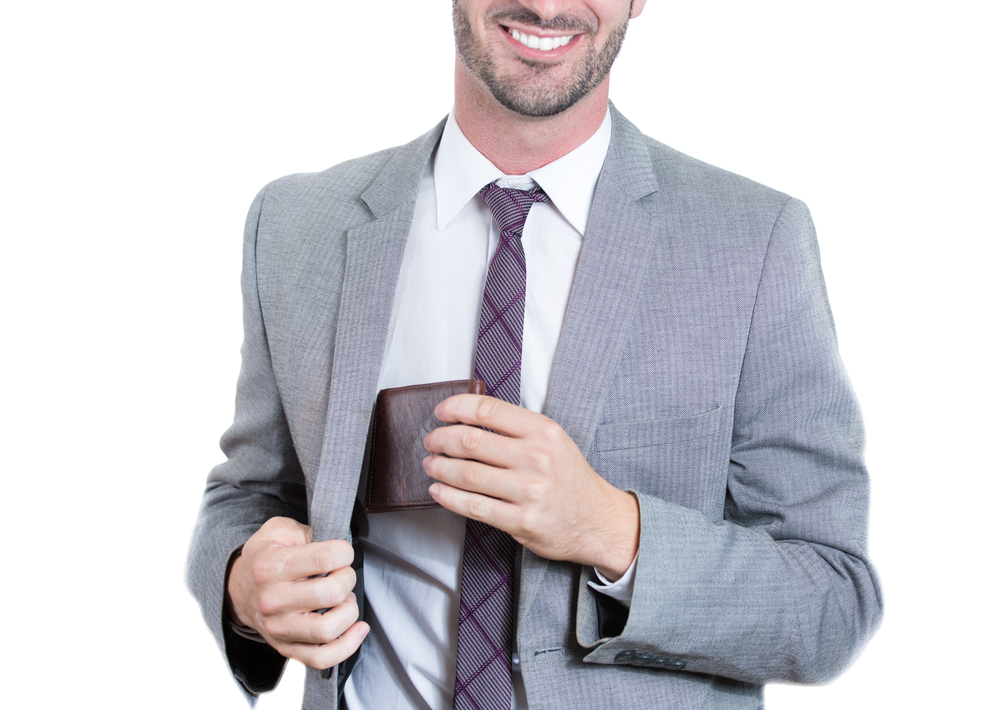 Closeup, cropped portrait of a smiling businessman reaching into his blazer pocket to get his wallet. Horizontal format isolated on white background. Business financial transaction