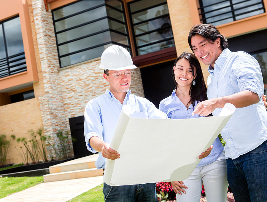 Couple buying a house and looking at blueprints