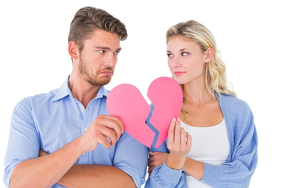 Couple holding two halves of broken heart on white background