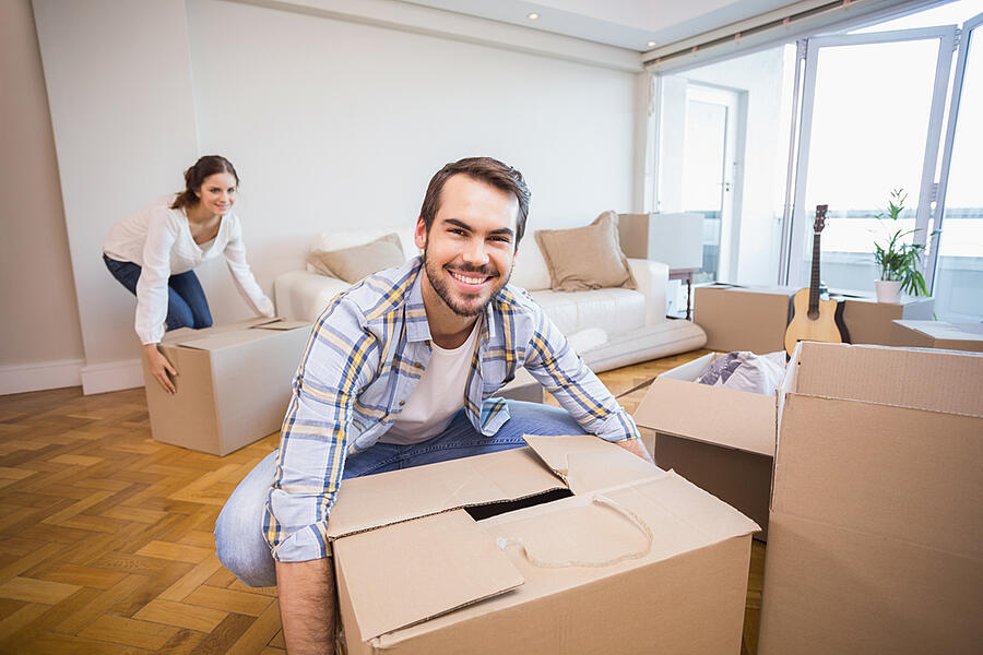 Cute couple unpacking cardboard boxes in their new home-1