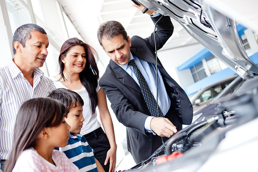 Family buying a car and looking at the engine