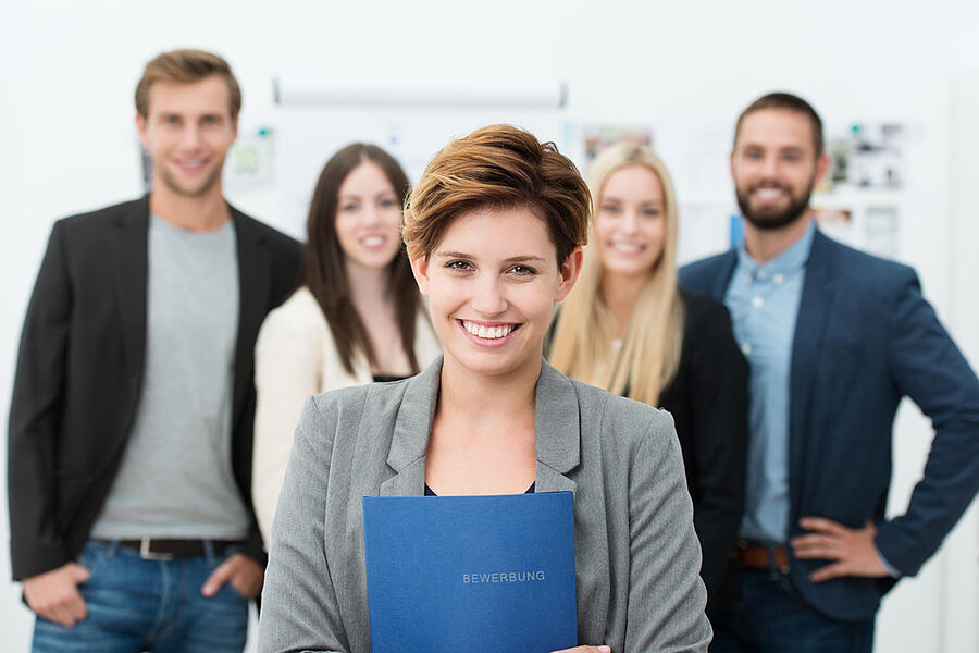 Group of job applicants with a smiling confident young woman in the foreground holding her Curriculum vitae in her hands