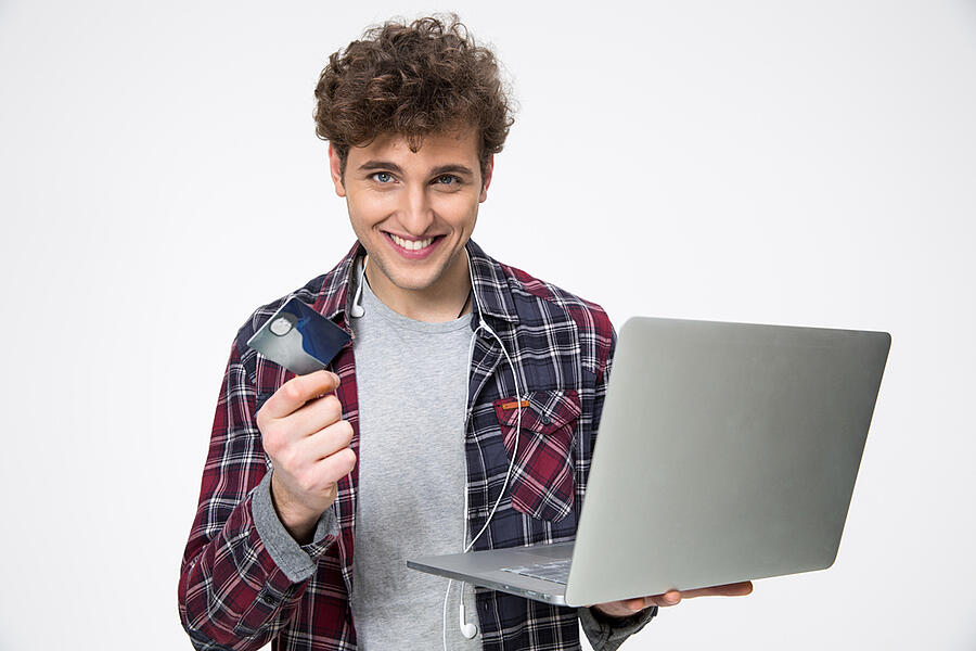 Happy casual young man standing with laptop and credit card