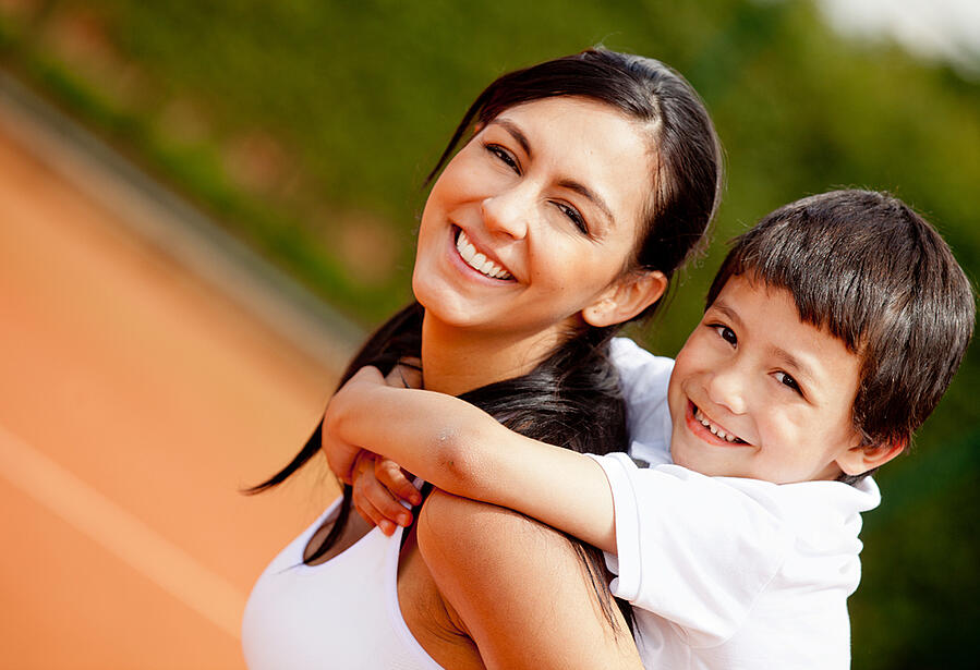 Lovely portrait of a mother and son at the tennis court