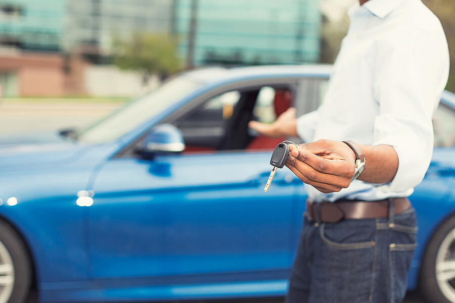 Male hand holding car keys offering new blue car on background-1