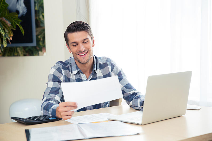 Portrait of a smiling man checking bills on the tablet at home