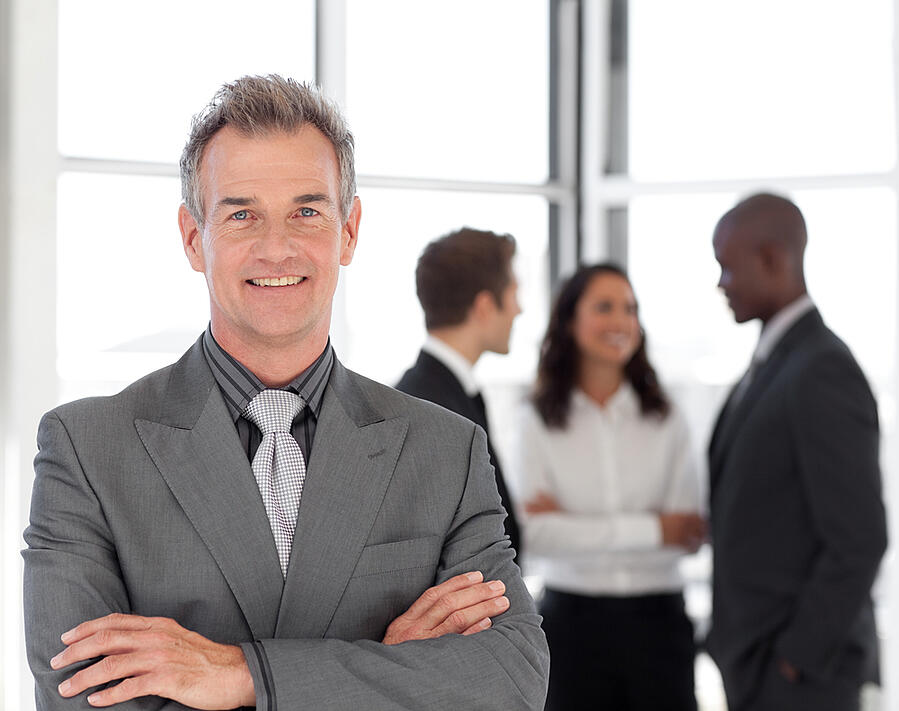 Senior Businessman being Positive with team in Background