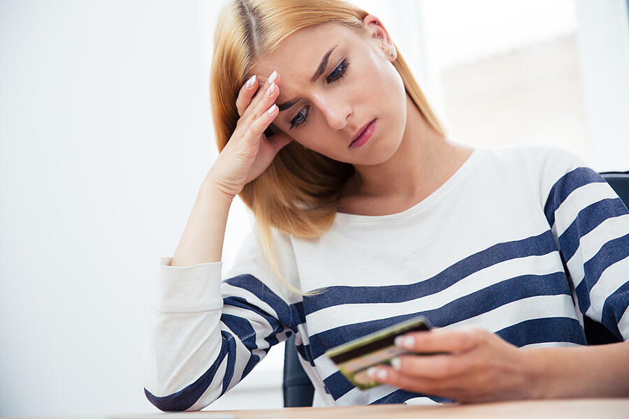 Unhappy casual woman holding bank card
