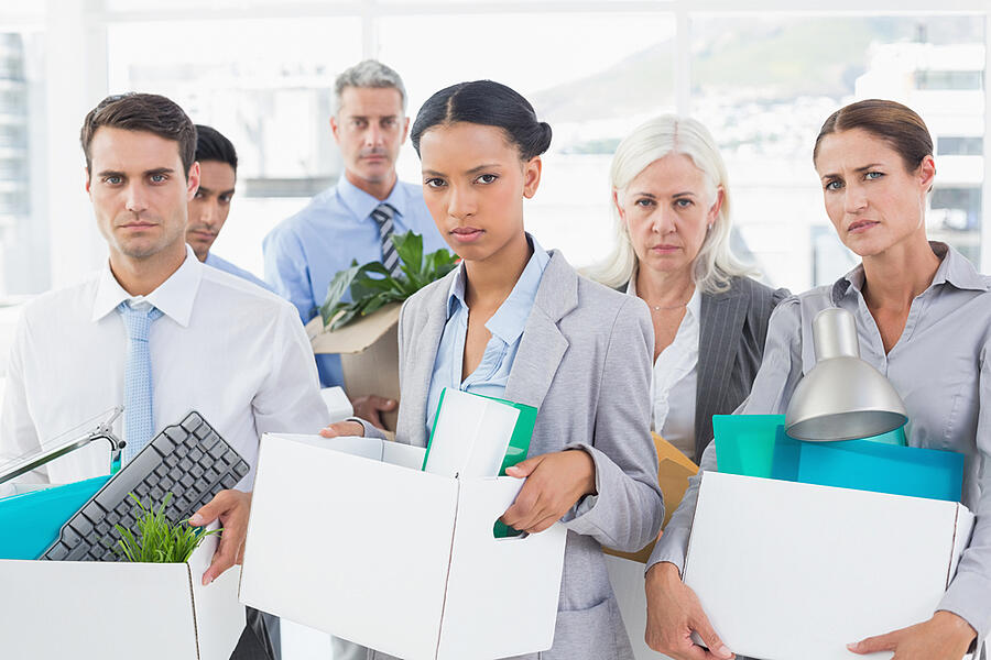 Unhappy fired business people holding box in office