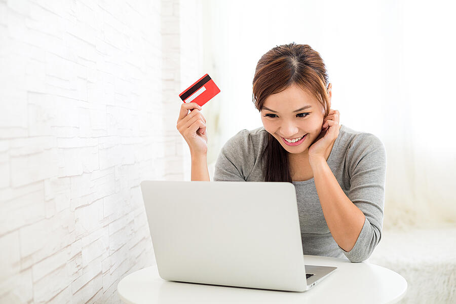 Woman enjoy online shopping paying by credit card