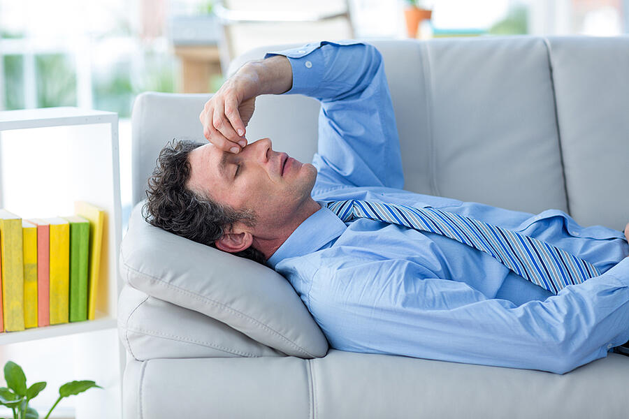 Worried businessman with head in hands lying on couch in living room