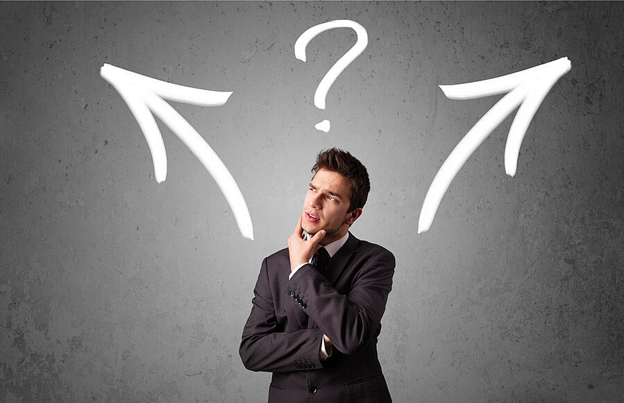 Young businessman taking a decision with arrows and question mark above his head