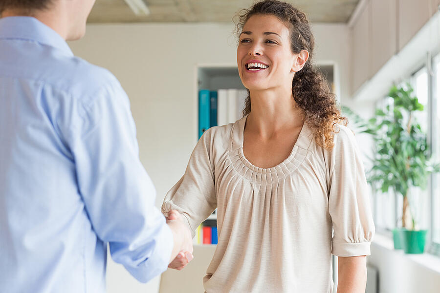 Young businesswoman shaking hands with male colleague in office
