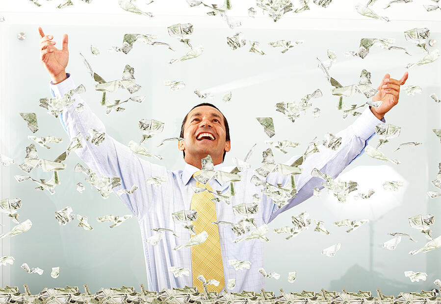 business success - man with lots of money smiling