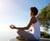 beautiful-young-woman-sitting-in-yoga-pose-at-beac-PK6JLLD