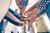 Handen op elkaar van collega's die gelukkig zijn en werken als een team