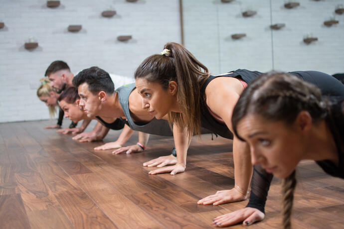 A fitness class with students in Plank Pose.