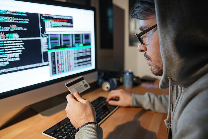 Concentrated young hacker in glasses stealing money from different credit cards sitting in dark room