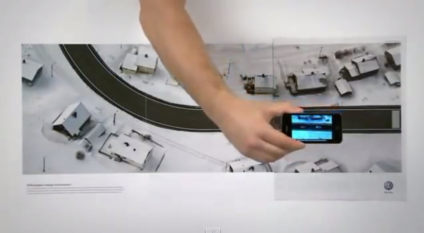 Interactive print advertisement by Volkswagon with three-page spread simulating a car test drive via smartphone