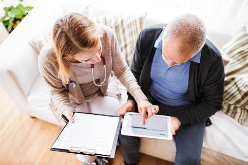 Health visitor and a senior man go over health on tablet during home visit.