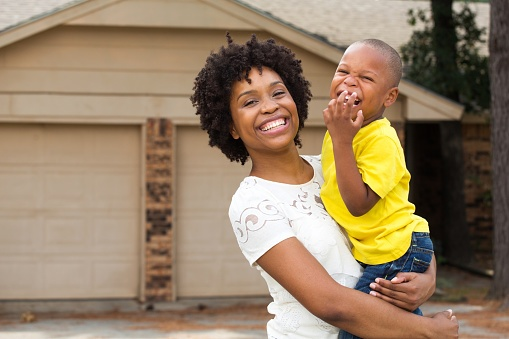 A mother smiles with her son in front of their garage.
