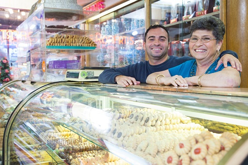 A photo of a middle aged mother and her son behind the counter of a family-owned pastry shop.